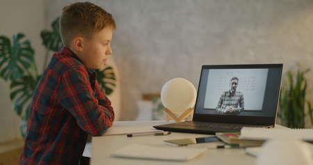 Medium shot of a boy falling asleep at his desk after having online maths class