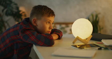 Medium shot of a boy changing color of table lamp by hitting on it