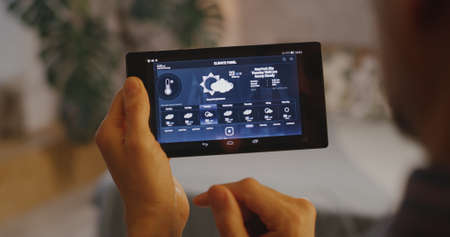 Close-up of a man checking various functions on a home hub