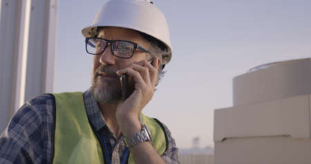 Medium close-up of an engineer having phone call on a cell tower Banco de Imagens