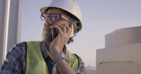 Medium close-up of an engineer having phone call on a cell tower 免版税图像