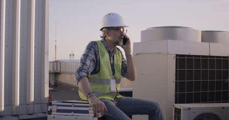 Medium shot of an engineer having phone call on a cell tower Banco de Imagens