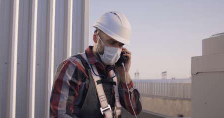 Medium shot of a face mask wearing engineer having a video call