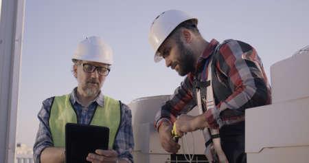 Medium shot of engineers talking while working on 5g antenna