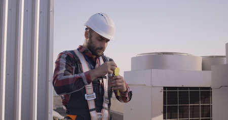 Medium shot of an engineer rolling up a cable