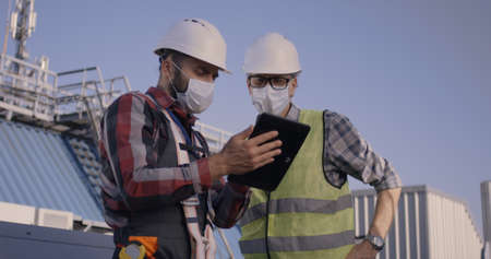 Medium close-up of engineers using a tablet while having a discussion