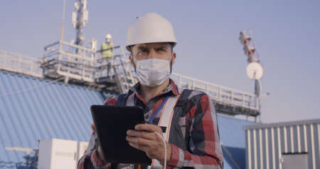 Medium shot of an engineer looking around while using a tablet on a cellular tower