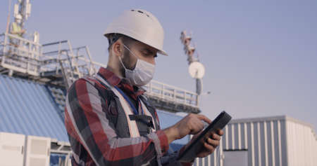 Medium shot of an engineer talking with his colleague while using a tablet on a cellular tower