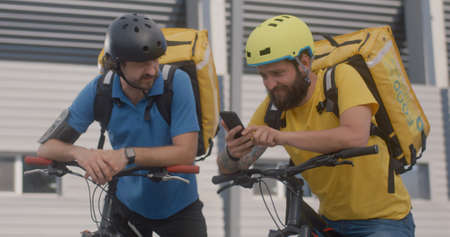 Medium shot of two bicycle messengers check smartphone before they ride away Standard-Bild