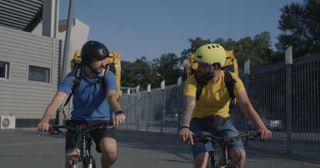 Medium shot of two bicycle messengers talk while ride bicycle Standard-Bild
