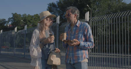 Tracking shot of a bicycle messenger delivers food and drink to a middle-aged couple