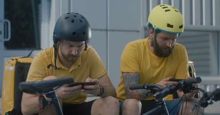 Medium close-up of bicycle messengers play mobile games just killing time between orders