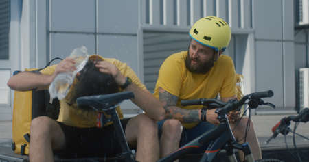 Medium shot of tired bicycle messengers take a break Banco de Imagens