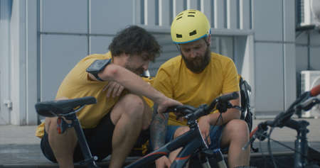 Medium shot of bicycle messengers discuss bicycles equipment Banco de Imagens - 153000234