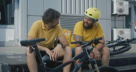 Medium shot of bicycle messengers discuss bicycles equipment