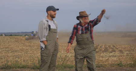 Tracking shot of senior man discussing agriculture with grandson while walking in field during plow Stock fotó