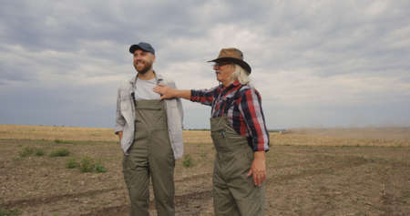 Pan around view of delighted elderly man demonstrating agricultural field after harvest to young successor