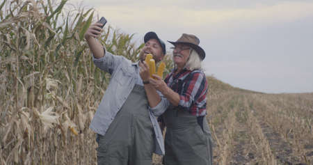 Grandfather and grandson with ripe corn ears taking selfie near dry plants while working in agricultural field together Stock fotó