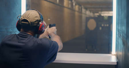 Back view of middle aged man shooting rifle fast then pushing button and waiting for target to move closer in range Stock fotó