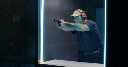 Middle aged man pushing button then reloading pistol and shooting while practicing in dark gallery