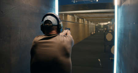 Back view of male in headset shooter firing pistol at target while practicing in shooting gallery Stock fotó
