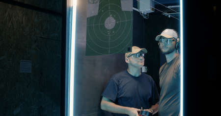 Low angle of men in goggles and caps inspecting and discussing target while practicing in dark shooting range together