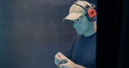 Concentrated middle aged male in goggles and headset reloading pistol and firing weapon in dark shooting gallery