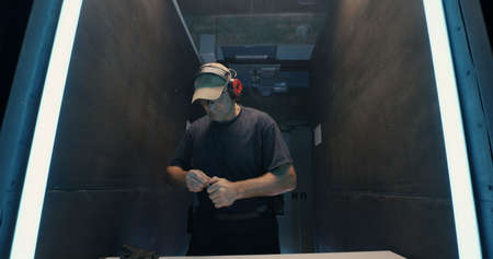 Zoom in and zoom out view of middle aged man reloading and shooting pistol then pushing button during practice in dark gallery