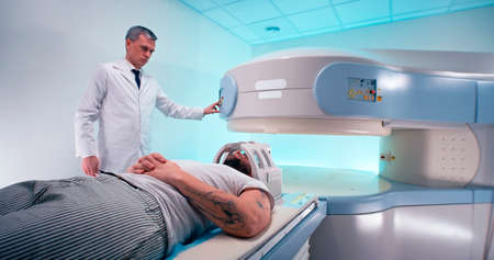 Middle aged medical practitioner releasing bearded man from MRI machine and taking off coil after brain scanning procedure in modern hospital
