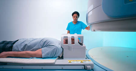 Elderly man lying on table while African American woman in scrubs fastening head coil and turning on MRI machine in lab of modern hospital