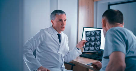 Mature man in medical robe showing MRI scans and talking with senior male patient while sitting at table with computer in laboratory