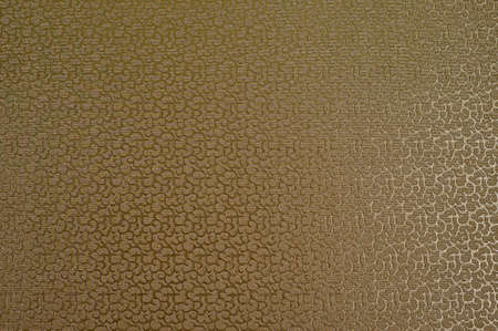 Texture of golden satin fabric with abstract embossing.
