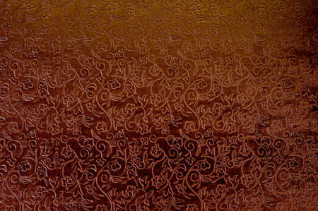 Texture of red satin fabric with floral embossing. Standard-Bild