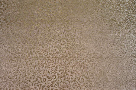 Texture of golden satin fabric with floral embossing.