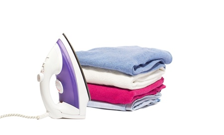 ironing: iron and a pile of clothes on a white background Stock Photo