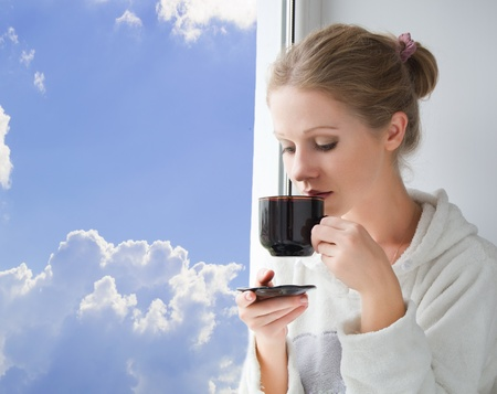 young beautiful girl drinking coffee by the window in the morning photo
