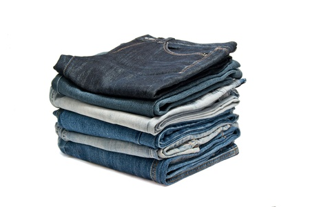 traditional clothes: Flat pile of jeans on a white background Stock Photo