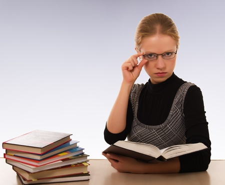Strict woman with a book sitting at table photo