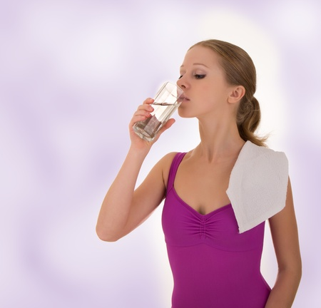 beautiful athletic girl drinks water after a workout photo