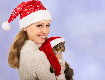 cute girl in a Christmas hat with cat Stock Photo - 10823155