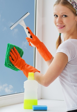 attractive young woman washing window