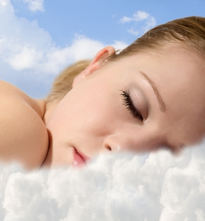 Portrait of a young girl sleeping  with  clouds photo