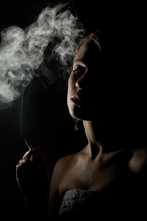 beautiful woman with a cigarette in the dark photo
