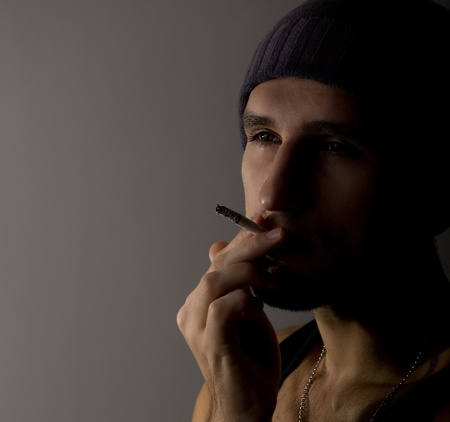 young man with a cigarette in the dark photo