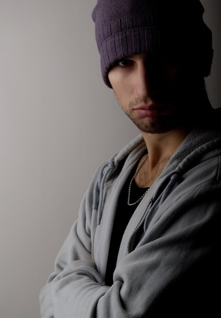 sad young man in a hat in the dark photo