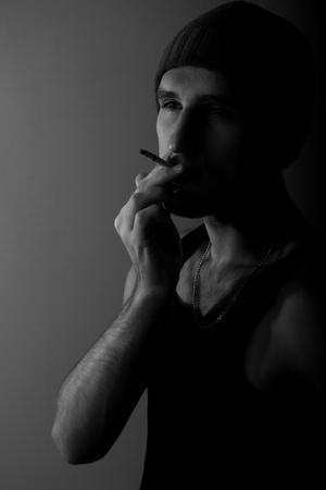 lonely young man with a cigarette in the dark photo