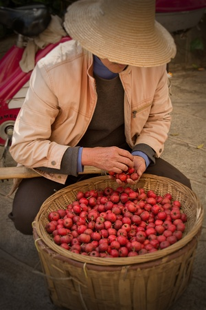 merchant: Asian man in  hat with small red apples