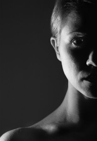 brooding: half of the  face of girl in the dark, monochrome Stock Photo