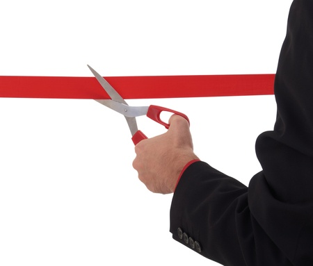 business man cutting a red ribbon, scissors photo