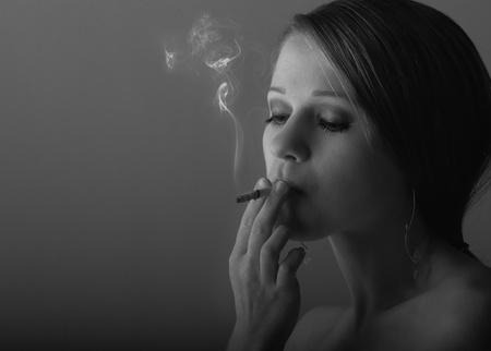 beautiful young woman smoking a cigarette  photo